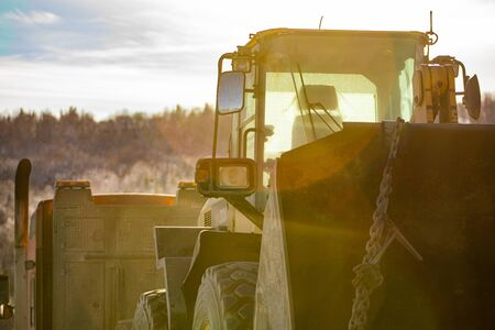 A close up abstract view of a construction excavator chained to an articulated lorry for transport. Low winter sun provides orange lens flare. Copy space to left