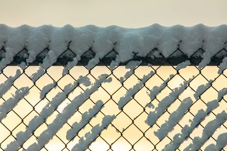 A close up soft focus shot of a chain link fence, aka diamond mesh, hurricane fencing, wire netting boundary, covered with snow during golden hour