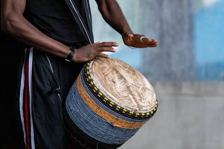 Closeup of african male artist wearing stripped pant and playing traditional african djembe drums while standing in world and spoken word festival