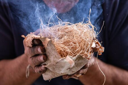 Closeup of man hand holding straw used as fire starter with smoke during demonstration of native traditional fire lighting in world and word festival