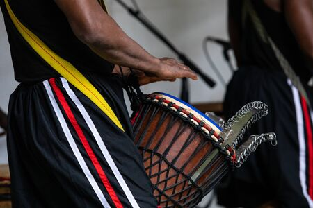 Closeup midsection of male artist wearing stripped pant and performing traditional african djembe drums in world and spoken word festival