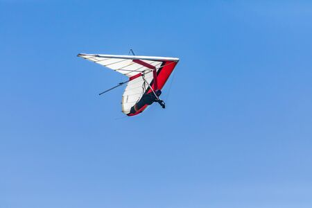 Hang-glider flying through the clear blue. Hang-gliding competition in Creston, British Columbia, Canada. Overhead view.