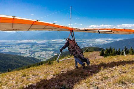 Le pilote de deltaplane prépare le décollage pendant le démarrage. Parapente homme courir pour survoler les montagnes de la vallée de Kootenay, Creston, Colombie-Britannique, Canada