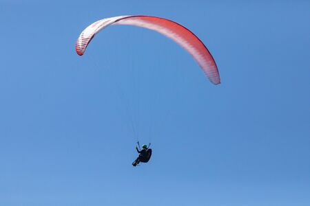 Alone paraglider flying in the clear blue sky. Paragliding in the sky on a sunny day. Long shot. Recreational and competitive adventure sport