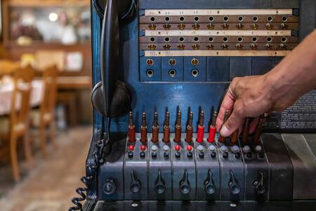 A hand touching old switchboard. Ancient telephone station in the museum. First phone station of the 20th century, Kootenays, British Columbia, Canada
