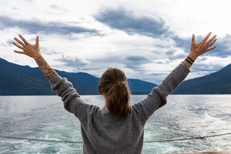 Close up from behind of a young long haired lady on the deck of a passenger ferryboat. Arms with tattoos wide open. Freedom concept and enthusiasm.