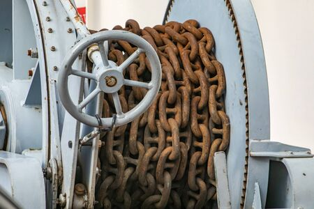 Old, rusty brown chain on a passenger ferryboat navigating in a canadian lake. Probably anchor chain. Industrial nautical equipment and instruments.