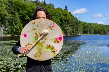 Closeup of long haired native american young man holding sacred native frame drum with fur covered stick at lake with waterlilies covering face
