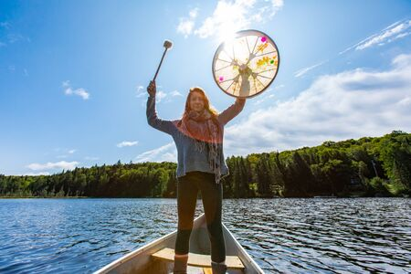 Low angle view of shamanic girl standing on canoe in lake holding sacred native frame drum with fur covered on stick in Northern Quebec, Canada