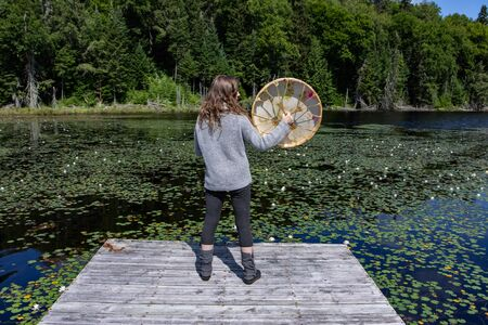 Full length rear view of young female standing on lake dock with waterlilies while holding sacred native frame drum in Northern Quebec in Canada