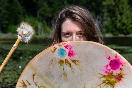 Closeup of beautiful woman holding sacred native frame drum with fur covered stick standing at lake with waterlilies covering face in Canada