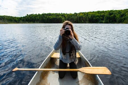 Young female photographer kneeling over knee is canoe clicking pictures with DSLR camera while on lake in Northern Quebec in Canada Banque d'images - 150519617