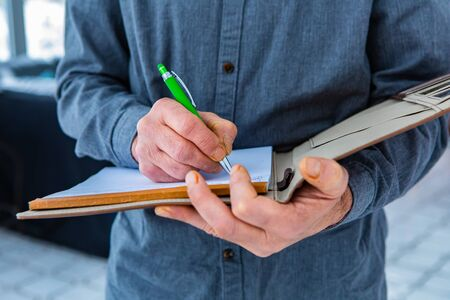 A close up and selective focus shot of a notebook with a leather cover held by inspectors hands with a green pen. as he taking and writes notes