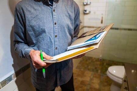 inspector holding a notebook, pen and his glasses as he checking the bathroom and shower, home checking and inspecting, interior inspection concept