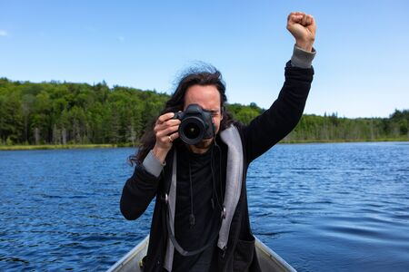 Long haired native american young man raising fist up in blue sly while shooting photos and videos using DSLR and sitting in canoe. riding in lake