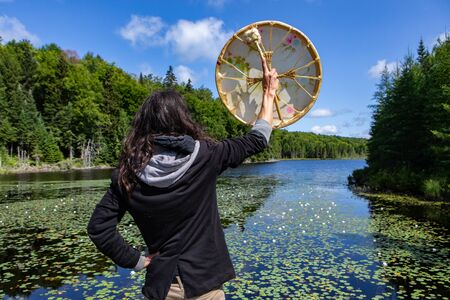 Rear view of long haired native american young man arms raised holding sacred frame drum while standing near lake with waterlily in Canada