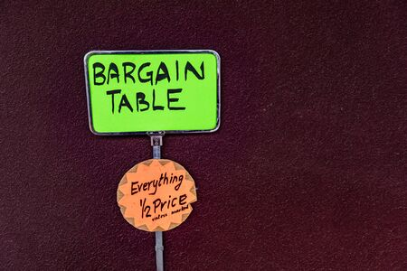 Hand written signs and price tags at the market. Yellow and orange fluo signs with black letters reading bargain table, half price. Dark red wall background. Banque d'images