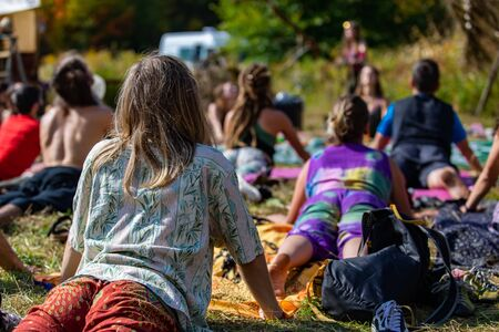A close up and rear view of a lady in Urdhva Mukha Svanasana, a back bending yoga posture during an earth festival celebrating mindfulness and culture