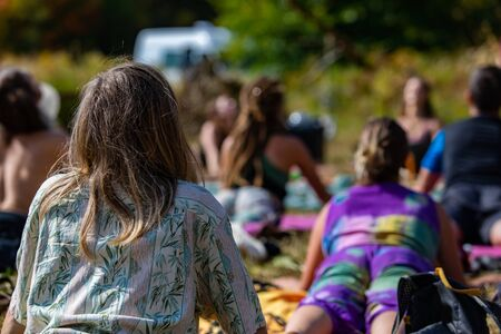Close up and rear view of a young woman in upward facing dog pose during a yoga class outdoor, with blurry people in background during earth festival