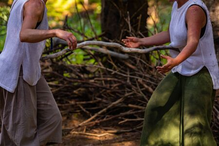 Two people are seen practicing ancient martial arts with a stick for distance training in a forest during a festival celebrating ancient tradition