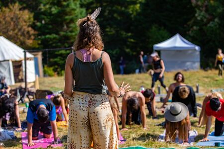 A spiritual guide is seen teaching people mindful yoga exercises in a forest clearing during a festival celebrating native culture and earth, copy space to right