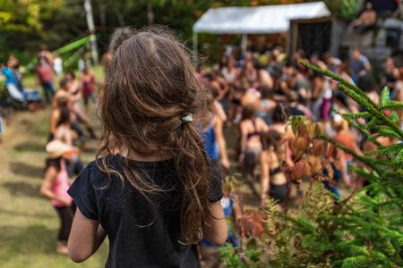 A close up selective focus view of a young girl with long brown hair watching a group of people do spiritual dance, during a festival celebrating earth