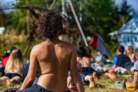 A close up and rear view on the back of a man during an outdoor yoga session at a festival celebrating mindfulness and diverse culture. Copy space to right