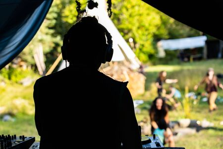 A close up and rear view of a silhouetted music DJ performing on stage. Backlit shot of musician wearing headphones with blurry people in background