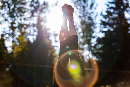 An abstract view on the legs of a girl doing a handstand during a mindful yoga session in nature, backlit sun shining through trees with lens flare Archivio Fotografico