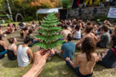 A first person perspective with shallow depth of field of hand holding a green fern leaf. as a blurry mixed group of people practice guided meditation Archivio Fotografico
