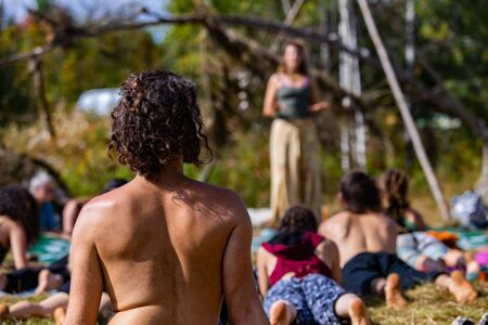 A close up and rear view in the bare back of a topless man doing sacred yoga in woodland during a multicultural festival, with blurry instructor in background