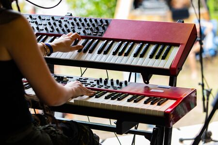 A close up selective focus shot on the hands of a woman playing two electronic keyboards on stage during a festival celebrating acoustic sounds