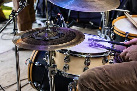 A close up view of a drum kit and the legs and hands of a drummer playing on stage. during a folk music set at an alternative communities festival Standard-Bild