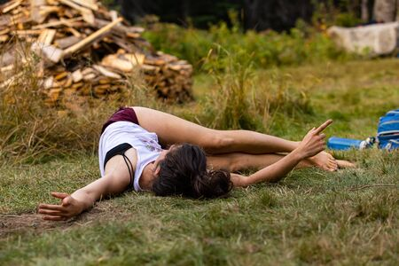 A young caucasian woman is seen in a calm and relaxed state during a mindful yoga and meditation session. in a forest clearing with copy space to right