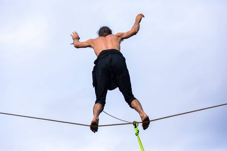 A talented slackwire artist is seen performing from below, standing barefooted on a high wire with raised arms against a cloudy sky with copy space
