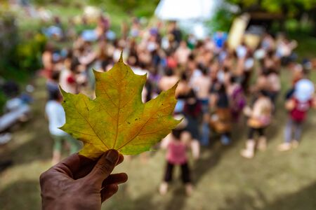 A first person selective focus view of a hand holding a green and yellow leaf near a large group of people, standing in a forest clearing at earth festival