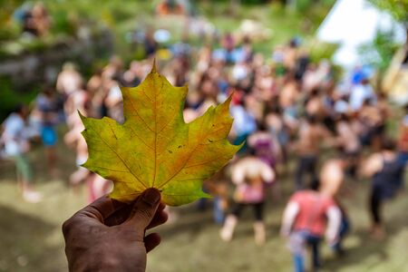 Closeup shot with shallow depth of field on a hand holding an autumnal leaf, against a blurry background of people doing guided yoga at earth festival