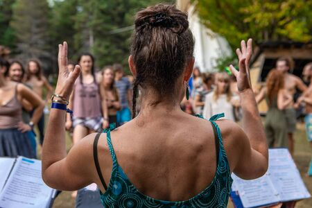 A close up selective focus shot of a sacred dance tutor with raised arms, seen from behind, guiding people through sacred dance at earth festival Archivio Fotografico