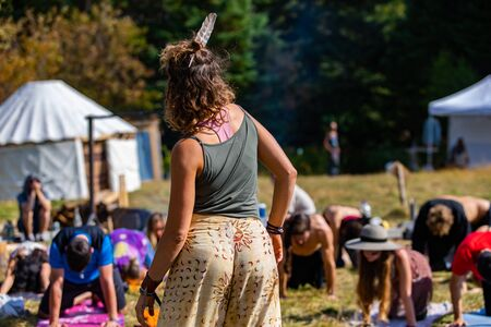 A mindful spiritual yoga teacher is seen from behind, with blurry students in background, wearing a native eagle feather in hair symbolizing strength Archivio Fotografico - 140636120