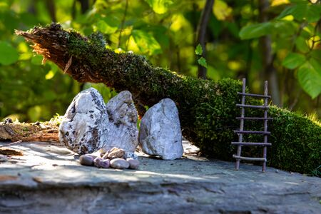 A close up selective focus view of a miniature magical fairy town scene in woodland, with moss covered log, handmade ladders, rocks, blurry trees in background
