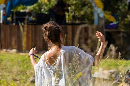 An elegant woman wearing a white flowing dress is seen from behind in selective focus, dancing and swaying arms during multicultural earth festival
