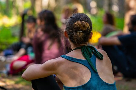A slim toned caucasian woman is seen from behind in shallow focus, sitting around a campsite with blurry people in background during earth festival