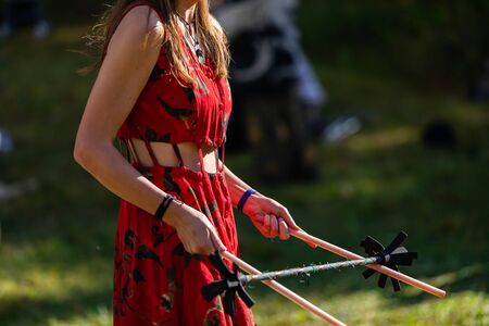 A closeup mid section shallow focus view of a slim caucasian woman entertaining people with devil sticks and flower pendulum at multicultural festival