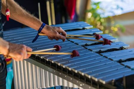 A close up soft focus shot on the hands of a man using four mallets to play a vibraphone instrument similar to a glockenspiel, copy space to right