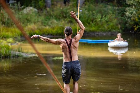 A man is seen from behind with shallow depth of field exercising core muscles walking a slackline in nature during an earth festival, copy space to sides