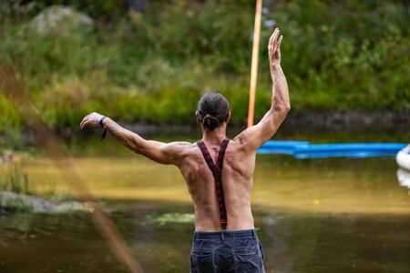 A slackwire performer is seen balancing on a slack rope over a green pond at a forest campsite during a festival celebrating earth and culture. Selective focus shot Standard-Bild