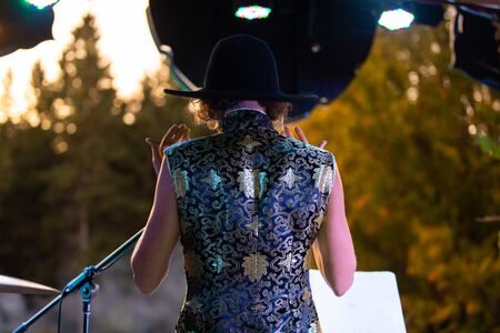 A close up and rear view with shallow depth of field from behind a woman, performing spiritual music on stage during a multicultural earth festival