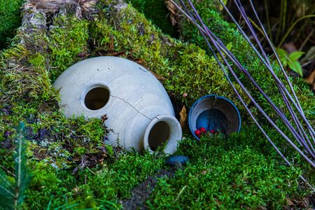 A close up shot of a magical fairy house in a forest, with moss covered tree stump, overturned stone urn, red berries, twigs. Copy space to right