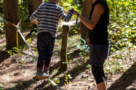 A caring mother is seen teaching a young boy how to balance on a slackline, anchored between two trees during a festival celebrating earth and culture