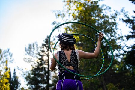 A low angle shallow focus shot of a lady dancing in a forest with two hoop rings during a festival celebrating people and culture. Copy space to sides